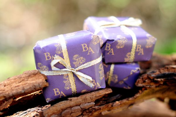 Bella Ann soap wrapped on a log
